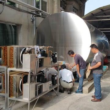 Dairy farm service team working on tank